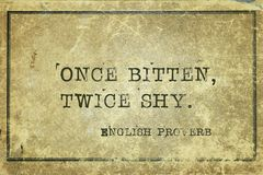Once bitten EnP. Once bitten, twice shy - ancient English proverb printed on grunge vintage cardboard royalty free stock images