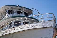 Party boat that has seen her last party. The once proud fishing vessel sits forgotten at the back of the boat yard Stock Photography