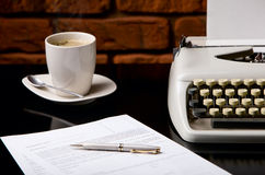 Once upon a time... Old fashioned morning scene: antique typewriter, cup of fresh coffee, business contract and pen Royalty Free Stock Photo