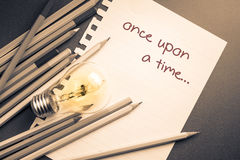 Once upon a time. On paper with pencils and lightbulb Royalty Free Stock Photo