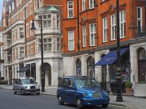 London cabs in Mayfair. The once ubiquitous black cabs of London are being replaced with more modern and colorful minicabs, as seen on Mount Street in Mayfair Stock Images