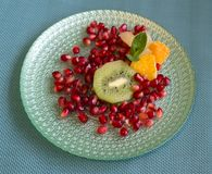 Pomegranate with pieces of kiwi, mandarin and grapefruit, with a mint leaf accent. royalty free stock images