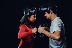 oncept av konkurrens och konfrontation Par av pro-gamers med VR-hörlurar med mikrofon deltar i den modiga striden arkivbilder
