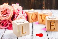 Oncept de jour de valentines : bougies brûlantes et amour de mot fait de bougeoirs en bois Images stock