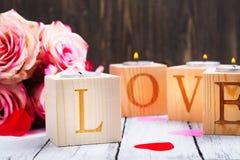 Oncept di giorno di biglietti di S. Valentino: candele brucianti ed amore di parola fatto dei supporti di candela di legno Fotografia Stock