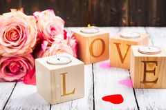 Oncept di giorno di biglietti di S. Valentino: candele brucianti ed amore di parola fatto dei supporti di candela di legno Immagini Stock