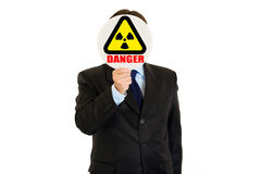 Сoncept-radiation danger! Man with radiation sign. Danger! Businessman holding  radiation sign in front of face isolated on white Royalty Free Stock Photography