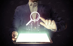 Сoncept search engine optimization. Image of a man with tablet in his hands and search icon. Сoncept search engine optimization, customer support Royalty Free Stock Image