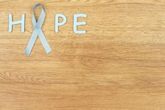 Oncological disease concept. Word `hope` written with the light blue ribbon as a symbol of prostate cancer in the corner of the wooden background Stock Image