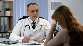 Oncologist informing woman about incurable disease, patient feels depressed stock image