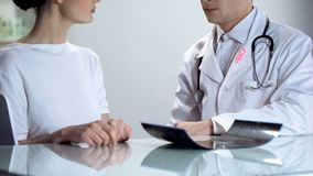 Oncologist with pink ribbon informing female patient about mammogram result stock image
