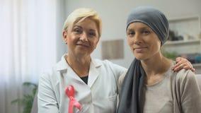 Oncologista e paciente que sofre de câncer que olham na câmera, esperando para a sobrevivência cura filme