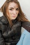 Ond flicka med långt hår i läderomslag fotografering för bildbyråer