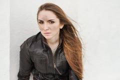 Ond flicka med långt hår i läderomslag royaltyfria foton
