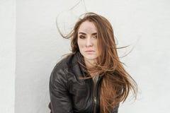 Ond flicka med långt hår i läderomslag royaltyfri fotografi
