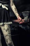 Ond kvinna som rymmer en blodig yxa Arkivfoton