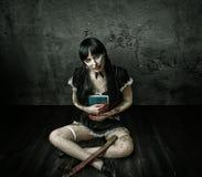 Ond kvinnainnehavbok och blodig yxa Royaltyfri Bild