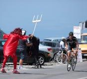 Ond maskot som väntar cyklisten Arkivfoton