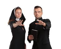 Ond präst och nunna på en vit bakgrund royaltyfri bild