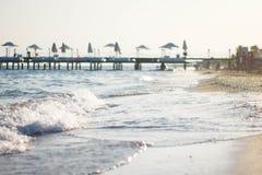 Onda branca no Sandy Beach A costa do mar azul contra o cais Cais pelo mar em Turquia imagens de stock royalty free