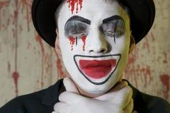 Onda clownhänder vid halsen på en väggbakgrund Royaltyfria Foton