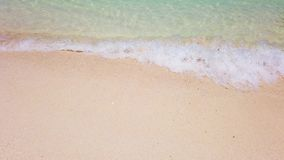 Onda con la espuma blanca en la playa blanca de la arena y la agua de mar clara Puede ser utilizado como fondo de las vacaciones  almacen de metraje de vídeo