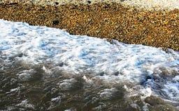 Onda de água com seixo em terra Imagens de Stock Royalty Free