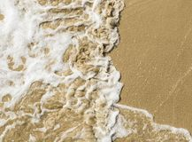 Onda de fractura apacible en una playa arenosa imagenes de archivo