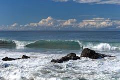 Onda de fractura cerca de la l?nea de la playa con las rocas sumergidas imagen de archivo libre de regalías