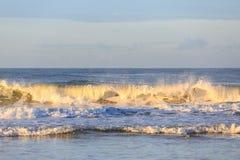 Onda de fractura en la playa en la puesta del sol Foto de archivo libre de regalías