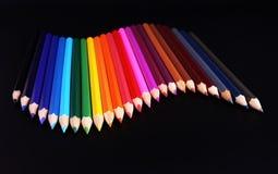 Onda de los lápices del color aislada en negro Fotografía de archivo libre de regalías