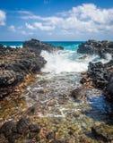 Onda de oceano que deixa de funcionar através de uma entrada rochosa Imagens de Stock Royalty Free