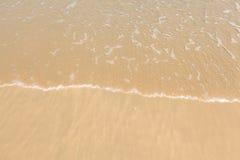 Onda del agua en la playa arenosa de oro clara Imagenes de archivo