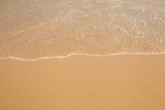 Onda del agua en la playa arenosa de oro clara Imagen de archivo
