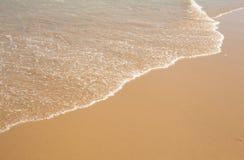 Onda del agua en la playa arenosa de oro clara Fotos de archivo
