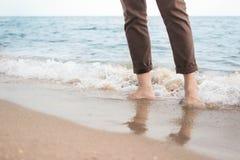 Onda del mar que se estrella en las piernas del hombre Imágenes de archivo libres de regalías