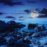 Onda del mare calmo sulla riva rocciosa alla notte Fotografie Stock Libere da Diritti
