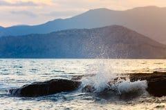 Onda del mare che spruzza sulle rocce sul primo piano della riva Andando al mare Tempo di festa fotografia stock