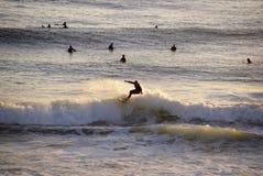 Onda del montar a caballo de la persona que practica surf, deportes acuáticos, paisaje de la puesta del sol Foto de archivo libre de regalías