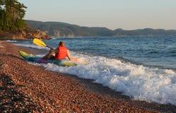 Onda del montar a caballo del Kayaker sobre la playa Fotos de archivo