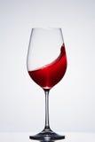 Onda del vino rojo de la bebida romántica en la copa pura que se opone a fondo ligero con la reflexión Fotografía de archivo libre de regalías