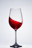 Onda del vino rojo en la copa frágil pura que se opone a fondo ligero con la reflexión Foto de archivo libre de regalías
