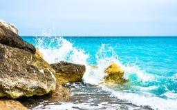 Onda dell'acqua di mare che spruzza sulle rocce della linea costiera fotografia stock