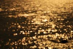 Onda do mar da ressaca de Blured no fundo claro dourado da praia do por do sol Foto de Stock