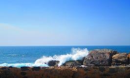 A onda do mar quebra em uma parede rochosa imagens de stock
