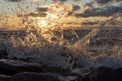 A onda do mar quebra sobre pedras, espirra no por do sol Fotos de Stock