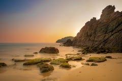 A onda e a alga longas da exposição em rochas na maré baixa e em cenário de colorido do céu e do mar lá são penhascos altos no cr fotografia de stock royalty free