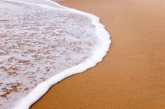 Onda e areia Fotos de Stock