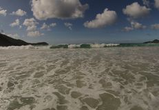 Onda espumosa de la playa con los cielos azules Imagen de archivo