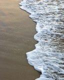 Onda espumosa na areia fotografia de stock